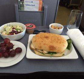 Kyllingesandwich serveret på United First Class. Tør og kedelig, men tilhørende salat og vindruer, som på ingen måde kunne betegnes som friske. Men i det mindst var sandwichen lun.