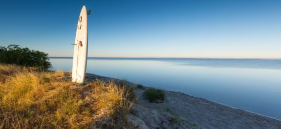 White surfing board pounded in sand on sea shore with golden sunrise light. Beautiful landscape of polish sea shore